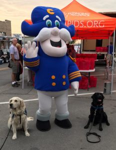 two service dogs in training with the captain crunch mascot
