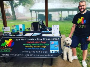 Volunteer with service dog in training at an event