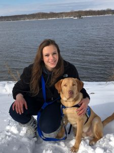 service dog in training with puppy raiser from Augustana College's club Viking Pups